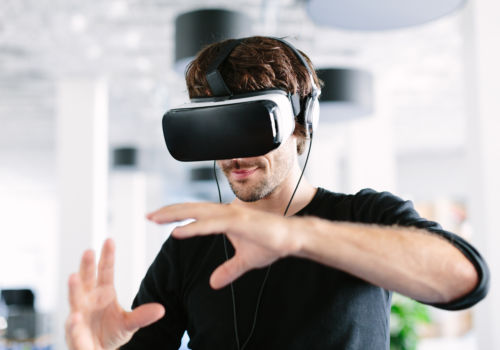 Young man wearing virtual reality glasses and gesturing in office